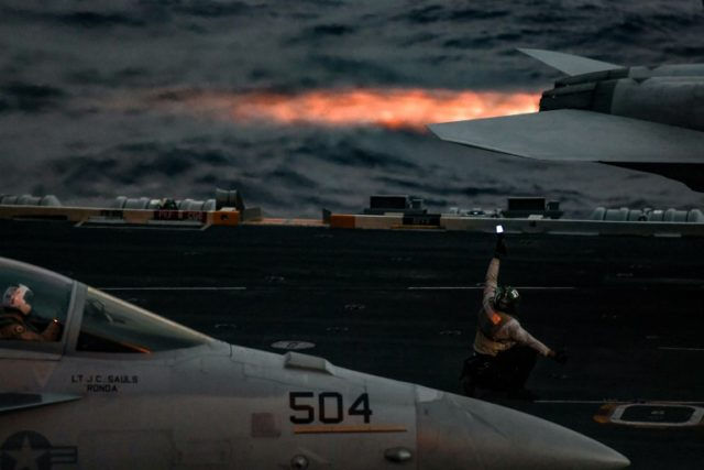 A crew member aboard the US navy aircraft carrier Harry S. Truman gestures as an F18 Super Hornet fighter jet waits to take off