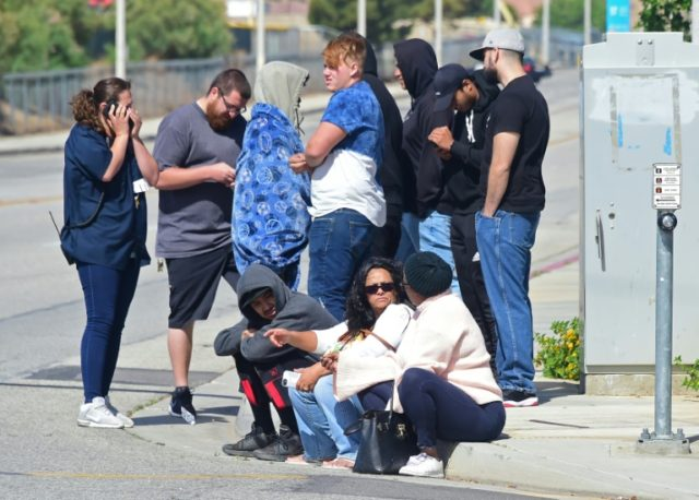 People wait at an intersection following reports of a shooting at nearby Highland High School in Palmdale, California