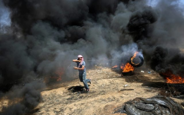 A demonstrator moves a burning tyre during protests on the Gaza border on May 11, 2018