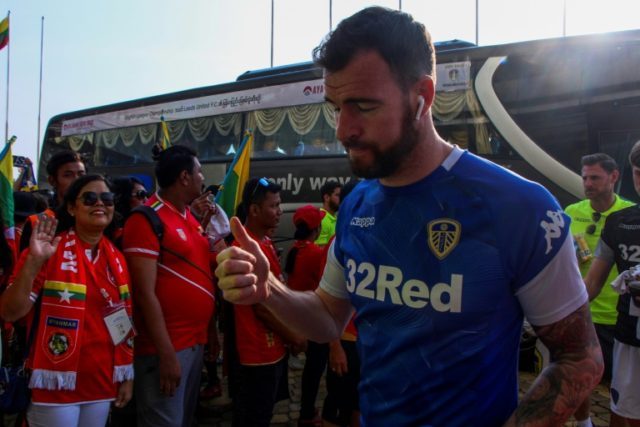 Leeds goalkeeper Andy Lonergan gives the thumbs up to fans as the team arrive for a friendly against Myanmar in Mandalay