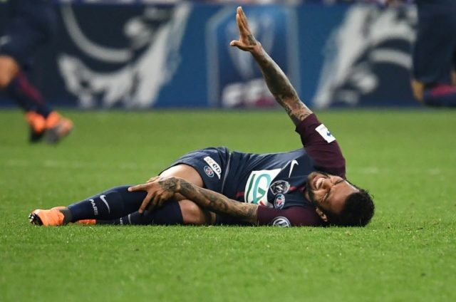 All over: Brazilian defender Daniel Alves gestures as he lies on the ground during the French Cup final with a knee injury which has ruled him out of the World Cup