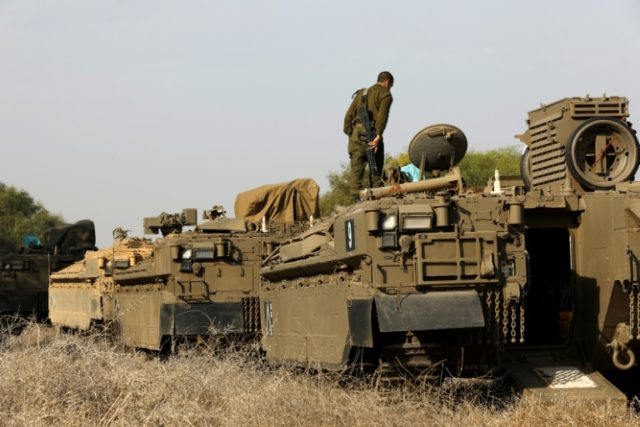 An Israeli soldier stands on an armoured personnel carrier (APC) as troops are on alert along the border with the Gaza Strip on November 13, 2017