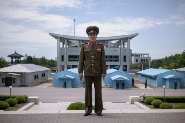 A North Korean soldier stands before the military demarcation line separating the two Koreas, with 'Peace House' - where the summit will take place - in the background on the right