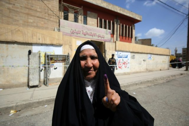 An Iraqi voter shows her ink-stained finger after casting her vote at a polling station in the city of Mosul on May 12, 2018