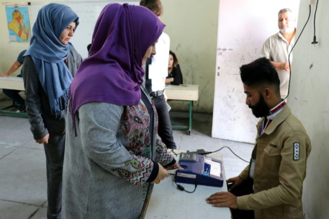 An Iraqi voter has her biometric voting card checked with her fingerprint upon arriving at a poll station in Iraq's northern city of Kirkuk on May 12, 2018