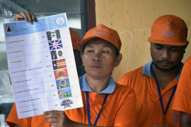 An election committee member holds up a ballot during vote tallying