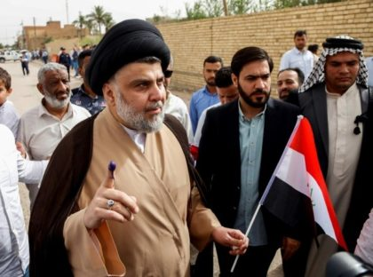 Iraqi Shiite cleric and leader Moqtada al-Sadr (C-L) outside a polling station in the central city of Najaf on May 12, 2018