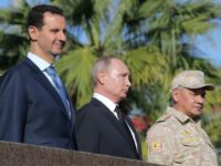 Russian President Vladimir Putin, his Syrian counterpart Bashar al-Assad and Russian Defence Minister Sergei Shoigu inspect a military parade during a visit to a Russian air base in Hmeimim