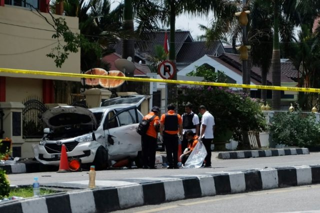 Indonesian policemen examine a car used by attackers during an assault on a police headquarters on the island of Sumatra that left one officer dead and two wounded