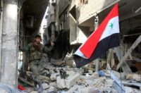 A member of the Syrian government forces poses for a photo next to a Syrian flag in destroyed buildings at the entrance of the Palestinian camp of Yarmuk on the southern outskirts of Damascus on May 21, 2018