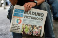 A man holds a newspaper referring to the victory of re-elected President Nicolas Maduro in the Venezuelan presidential election in Caracas.