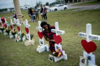 Jai Gillard, a freshman who was in the class where the mass shooting started, looks at a cross for Sabika Sheikh before signing it at a memorial for the victims of the Santa Fe High School shooting on May 21, 2018