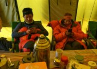 Climbers on their mobile phones while waiting at Everest base camp, where hipster perks and modern conveniences have replaced the deprivations of the past