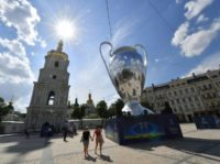 People walk past a huge trophy set in the Ukrainian capital of Kiev on May 25, 2018, a day before of the 2018 UEFA Champions League Cup final football match between Real Madrid and Liverpool FC