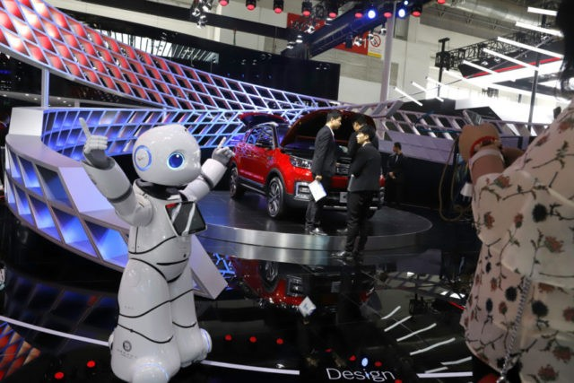 """In this April 26, 2018, photo, a robot entertains visitors at the booth of a Chinese automaker during the China Auto 2018 show in Beijing, China. Under President Xi Jinping, a program known as """"Made in China 2025"""" aims to make China a tech superpower by advancing development of industries …"""