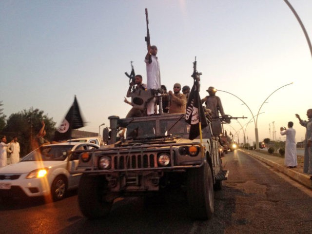 In this June 23, 2014 file photo, fighters from the Islamic State group parade in a commandeered Iraqi security forces armored vehicle on the main road in Mosul, Iraq. In a statement Thursday, May 10, 2018, coalition spokesman Army Col. Ryan Dillon said that U.S.-backed Syrian forces have captured five …