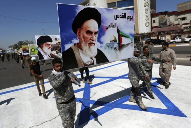 In this June 23, 2017 file photo, supporters of Iraqi Hezbollah brigades march on a representation of an Israeli flag with a portrait of late Iranian leader Ayatollah Khomeini and Iran's supreme leader Ayatollah Ali Khamenei, in Baghdad, Iraq. There may not be much Iran can do about President Donald …