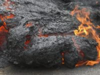 File - In this May 5, 2018, file photo, lava burns across a road in the Leilani Estates subdivision near Pahoa, Hawaii. The lava hisses, crackles and pops. It roars like an engine as it sloshes and bubbles. It shoots into the sky, bright orange and full of danger, or …