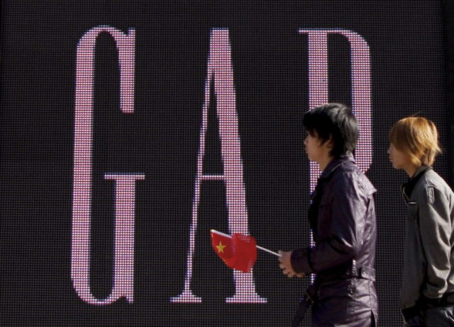 "In this Nov. 16, 2010 file photo, a man carries a Chinese flag as he walks past U.S. retailer GAP's newly-opened flagship store in Beijing. U.S. clothing retailer Gap has apologized Monday, May 14, 2018, for selling T-shirts with what it says was an ""erroneous"" map of China. (AP Photo/Andy …"