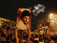 In this May 14, 2018, file photo, followers of Shiite cleric Muqtada al-Sadr, seen in the poster, celebrate in Tahrir Square, Baghdad, Iraq. Fourteen years after Muqtada al-Sadr's militias fought and killed American troops who had invaded Iraq, the United States is preparing to work hand in hand with the …