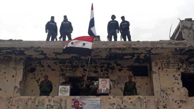In this photo released by the Syrian official news agency SANA, Syrian military and police forces fly their national flags on a damaged building and hold a picture of Syrian President Bashar Assad, in the Hajar al-Aswad neighborhood, southern Damascus, Syria, Tuesday, May 22, 2018. Syrian state TV said Tuesday …