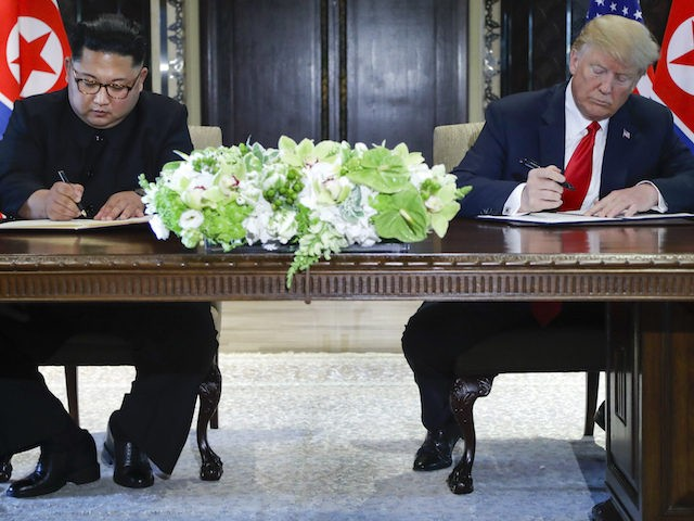 North Korea leader Kim Jong Un and U.S. President Donald Trump sign documents after their meetings at the Capella resort on Sentosa Island Tuesday, June 12, 2018 in Singapore. (AP Photo/Evan Vucci)