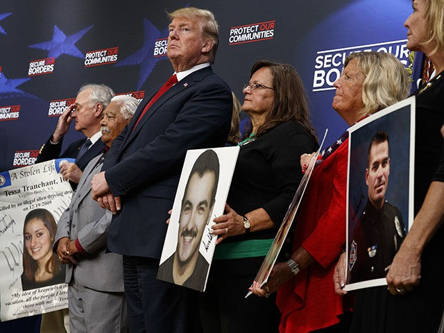 President Donald Trump stands alongside family members affected by crime committed by undocumented immigrants, at the South Court Auditorium on the White House complex, Friday, June 22, 2018, in Washington. (AP Photo/Evan Vucci)