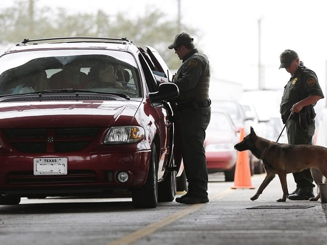 U.S. Customs and Border Patrol agents and K-9 security dog keep watch at a checkpoint station, on Feb. 22, 2013, in Falfurrias, Texas. Some drug smugglers caught at the highway checkpoint about an hour north of the Texas-Mexico border are losing their drugs, but not facing prosecution because cooperation between …