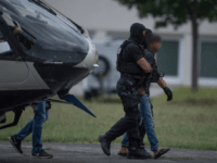 Police officers of a special unit escort Iraqi asylum seeker Ali Bashar, who is suspected of having killed a German teenage girl, from a helicopter to the police headquarters in Wiesbaden, western Germany, after he was flown back from Erbil to Germany on June 9, 2018. - The 20-year-old man …