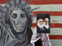 A pro-government Iranian female demonstrator, makes her way as she holds a poster showing pictures of the late revolutionary founder Ayatollah Khomeini, right, and supreme leader Ayatollah Ali Khamenei, at the conclusion of an annual demonstration in front of the former US Embassy in Tehran, Iran, Wednesday, Nov. 4, 2009, …