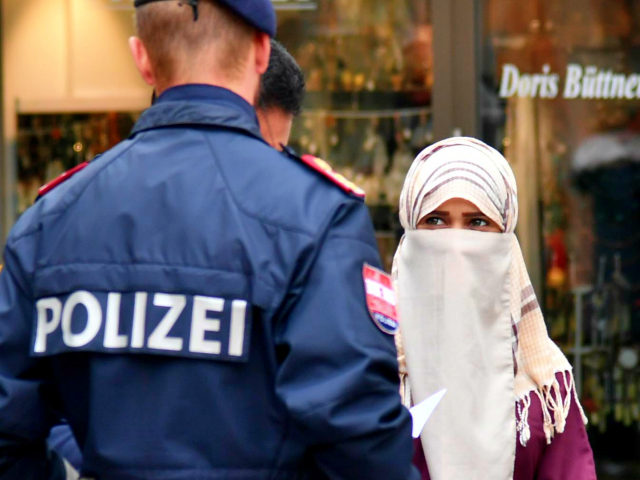 A police officer asks a woman to unveil her face in Zell am See, Austria, on October 1, 2017. Austria's ban on full-face Islamic veils comes into force following similar measures in other European countries. / AFP PHOTO / APA / BARBARA GINDL / Austria OUT (Photo credit should read …