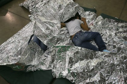 MCALLEN, TX - SEPTEMBER 08: A girl from Central America rests on thermal blankets at a detention facility run by the U.S. Border Patrol on September 8, 2014 in McAllen, Texas. The Border Patrol opened the holding center to temporarily house the children after tens of thousands of families and …