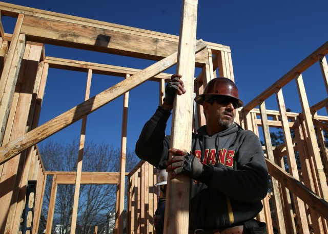 PETALUMA, CA - JANUARY 21: A worker carries lumber as he builds a new home on January 21, 2015 in Petaluma, California. According to a Commerce Department report, construction of new homes increased 4.4 percent in December, pushing building of new homes to the highest level in nine years. (Photo …