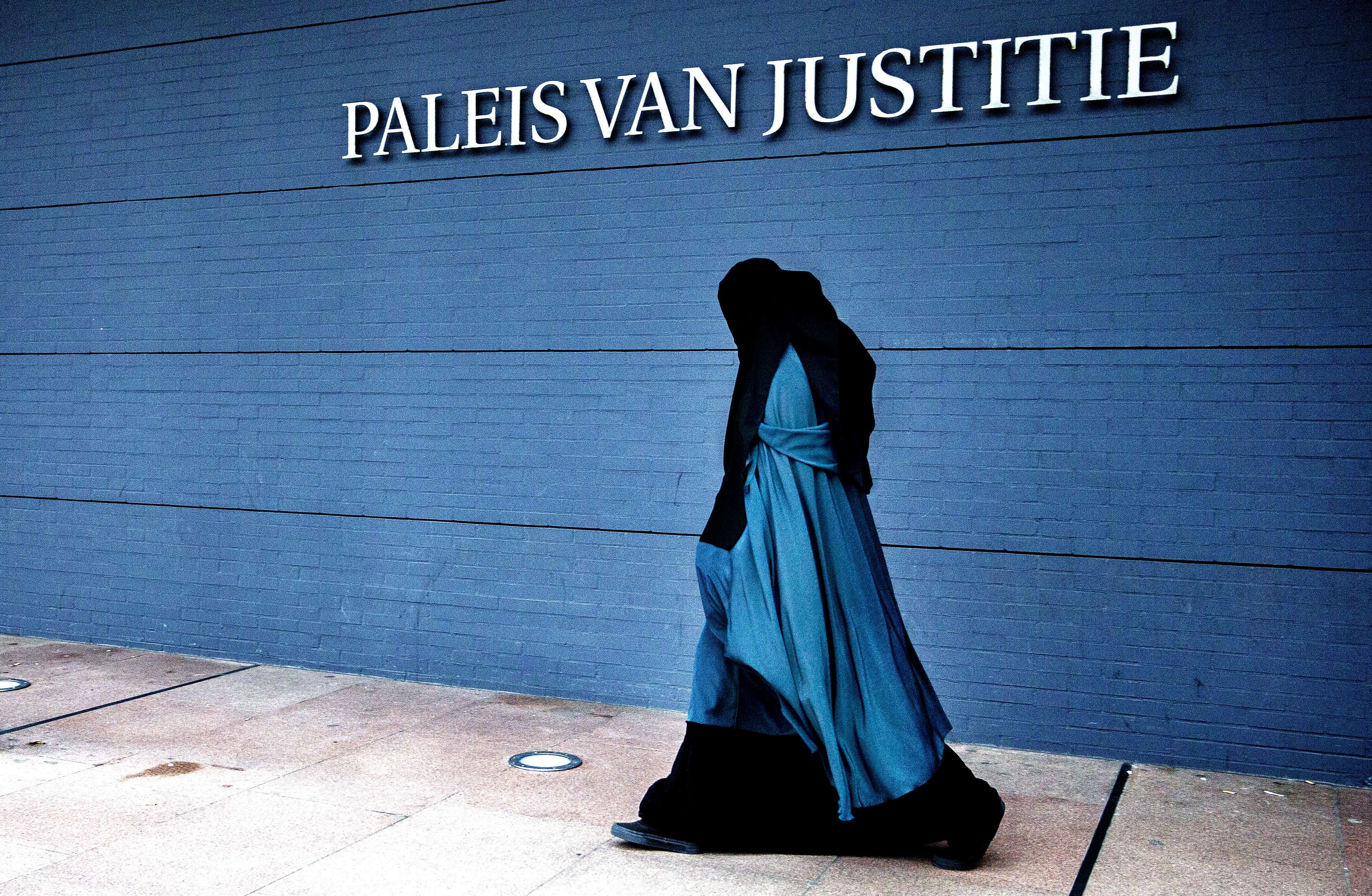 A woman wearing a burqa walks past the Palace of Justice in The Hague on December 1, 2014. The Dutch cabinet approved on May 22, 2015 a partial ban on wearing the face-covering Islamic veil, including in schools, hospitals and on public transport. AFP PHOTO / ANP PHOTO / FILER JERRY LAMPEN netherlands out (Photo credit should read JERRY LAMPEN/AFP/Getty Images)