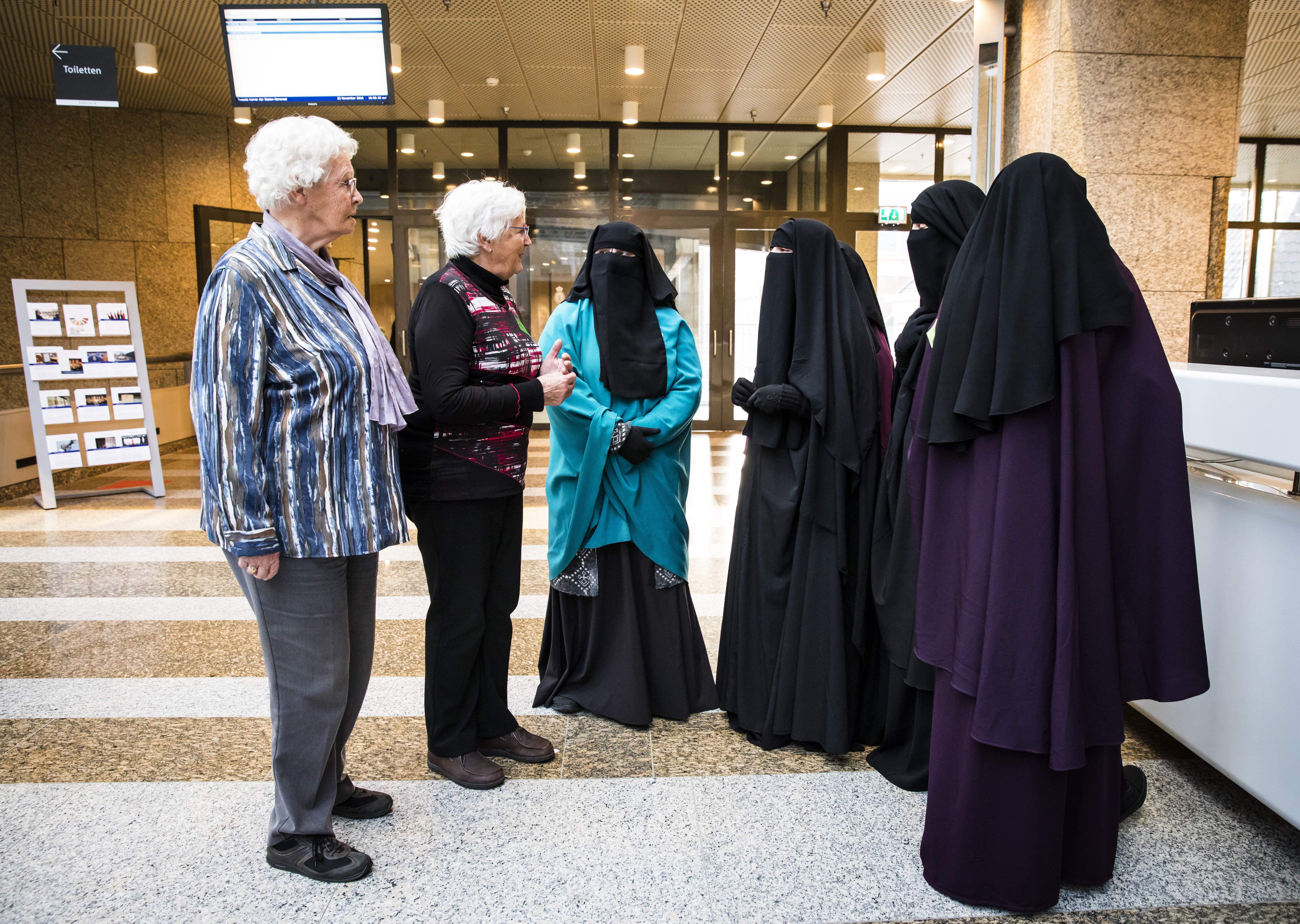 Two women stand next to women wearing niqab as they visit the Senate on November 23, 2016 in the Hague, the Netherlands.