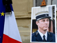a portrait of French Lieutenant-Colonel Arnaud Beltrame is pictured during a minute of silence, on March 28, 2018 at the Interior Ministry in Paris. France honours during a national ceremony on March 28 a heroic policeman who died offering himself as a hostage in a jihadist attack. Beltrame, 44, was …