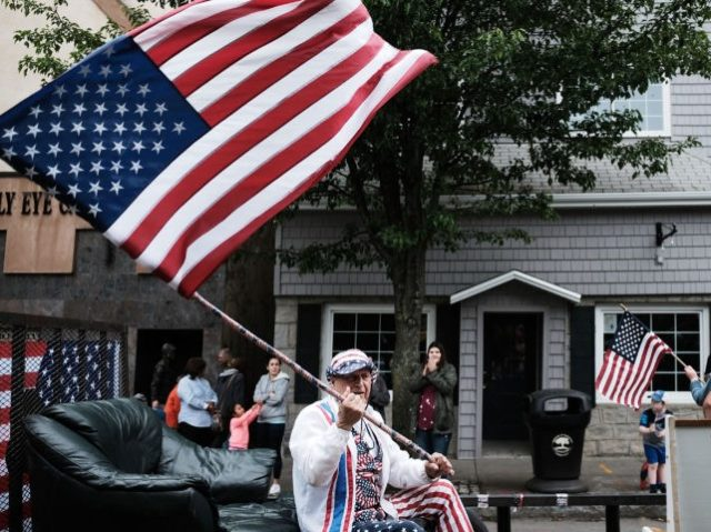 NAUGATUCK, CT - MAY 28: A man waves an American flag during the annual Memorial Day Parade on May 28, 2018 in Naugatuck, Connecticut. Across America, towns and cities will be remembering those who lost their lives while serving in the United States Armed Forces. Memorial Day is a federal …