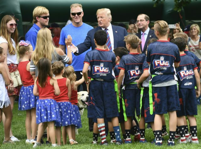 US President Donald Trump (C) interacts with children as people participate in the White House Sports and Fitness Day on May 30, 2018 in Washington,DC. (Photo by Nicholas Kamm / AFP) (Photo credit should read NICHOLAS KAMM/AFP/Getty Images)