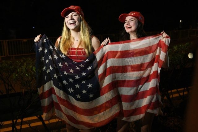 Erica Boland (R), a US student based in Singapore and a supporter of US President Donald Trump, and her friend wave a US flag as they wait for his arrival, outside the Shangrila hotel in Singapore on june 10, 2018. - Kim Jong Un and Donald Trump will meet on …