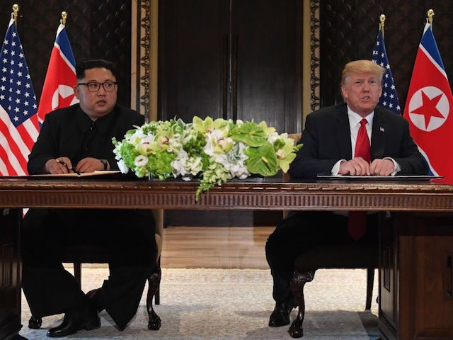US President Donald Trump (R) speaks while seated with North Korea's leader Kim Jong Un (L) at a signing ceremony during their historic US-North Korea summit, at the Capella Hotel on Sentosa island in Singapore on June 12, 2018. - Donald Trump and Kim Jong Un became on June 12 …