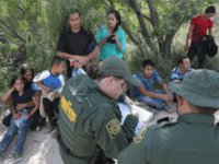 Central American asylum seekers wait as U.S. Border Patrol agents take groups of them into custody on June 12, 2018 near McAllen, Texas. The families were then sent to a U.S. Customs and Border Protection (CBP) processing center for possible separation. U.S. border authorities are executing the Trump administration's zero …