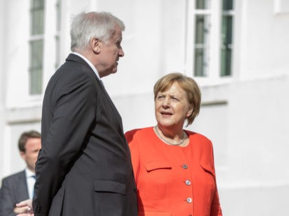 German Interior Minister Horst Seehofer (L) talks with Chancellor Angela Merkel as they arrive for a family picture before a French-German ministerial conference to coordinate European reform proposals ahead of EU summit on June 28-29, 2018 on June 19, 2018, at the Meseberg Palace, northeastern Germany. - German Chancellor Angela …