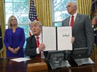 WASHINGTON, DC - JUNE 20: U.S. President Donald Trump, accompanied by Department of Homeland Security Secretary Kirstjen Nielsen (L) and U.S. Vice President Mike Pence (R), displays an executive order he signed that will end the practice of separating family members who are apprehended while illegally entering the United States …