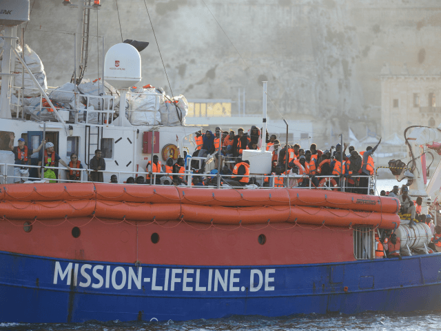 Migrants arrive aboard 'Lifeline', a vessel for the German charity Mission Lifeline, in the harbour of Valletta, Malta, on June 27, 2018. - A rescue boat stranded for nearly a week in the Mediterranean with over 200 migrants docked in Malta on June 27, 2018, after a deal was struck …