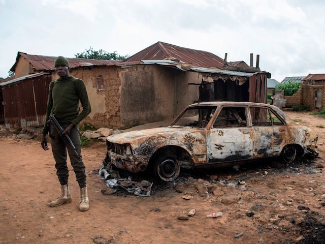 A member of the security forces stands next to a burnt out vehicle in the Nghar Village, near Jos on June 27, 2018, after Fulani herdsmen attacked the village. - Plateau State in Nigeria has seen days of violence where more than 200 people have been killed in clashes between …
