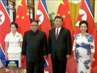 This image taken from China's CCTV on June 19, 2018, shows Chinese President Xi Jinping with his wife Peng Liyuan at right and North Korean leader Kim Jong Un with his wife Ri Sol-Ju at left during a welcome ceremony at the Great Hall of the People in Beijing. (CCTV …