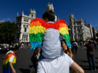 A child sporting rainbow wings is carried on shoulders in front of the Madrid city hall before the WorldPride 2017 parade in Madrid on July 1, 2017. Revellers took to the rainbow streets of Madrid today in the world's biggest march for gay, lesbian, bisexual and transgender rights. Carried along …