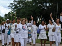 Members of the Cuban Human Rights group Ladies in White make an 'L' (of liberation) with their fingers as they march along the 5th Avenue in Havana, on November 7, 2010. The march demanded Cuban President Raul Castro to complete the liberation of 52 political prisoners, which deadline was today. …