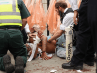 LONDON, ENGLAND - AUGUST 29: A man is given emergency medical treatment by police officers and paramedics after being stabbed in the stomach at the Notting Hill Carnival on August 29, 2011 in London, England. The annual carnival, which is the largest of its kind in Europe and is expected …