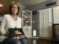 Mary Ann Mendoza poses for a photograph while holding a framed picture of herself and her son, Brandon Mendoza, on Thursday, March 2, 2017, at her home in Mesa, Ariz. Families who have lost loved ones to crimes committed by immigrants are praising President Donald Trump's announcement this week that …